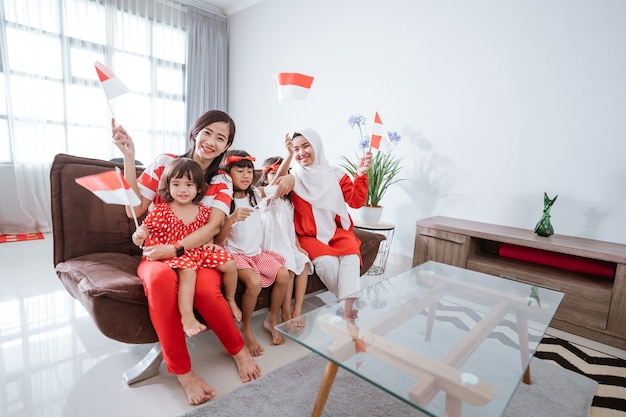 Mother and daughter celebrating indonesian independence day at home wearing red and white with indon...