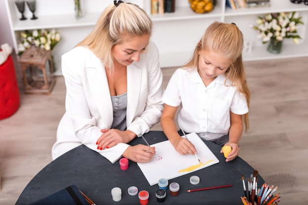 Mother and daughter child drawing and painting together