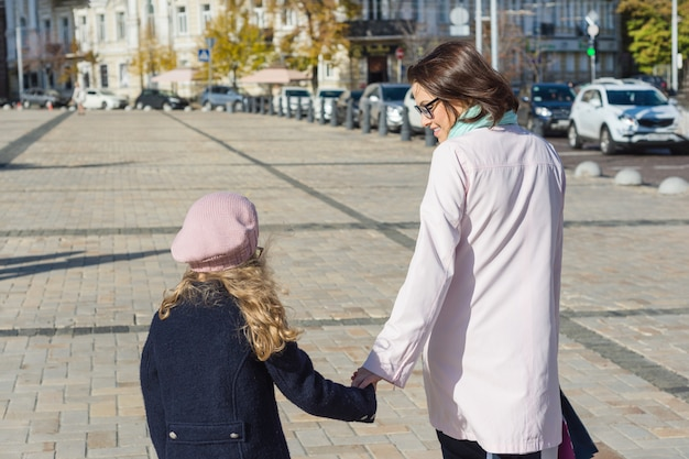 Mother and daughter child hold hands walk