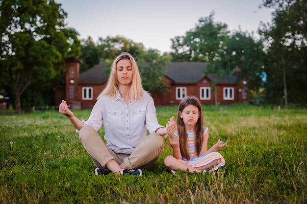 Mother and daughter child meditate together in lotus position outdoors.