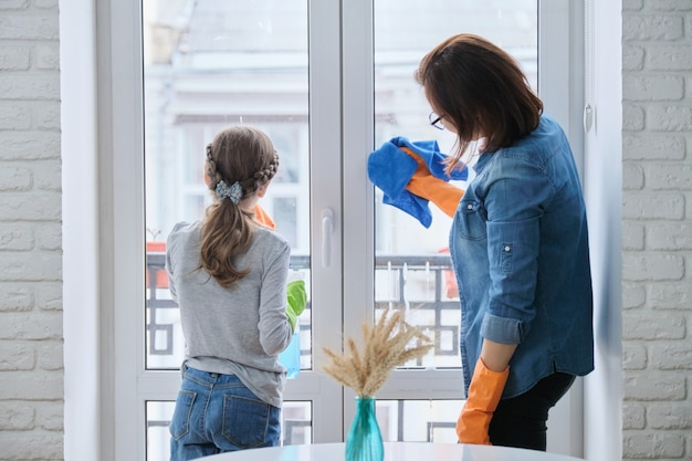 Mother and daughter child in rubber gloves with detergent and rag washing windows together. girl helping woman do house cleaning