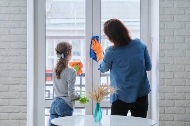 Mother and daughter child in rubber gloves with detergent and rag washing windows together.