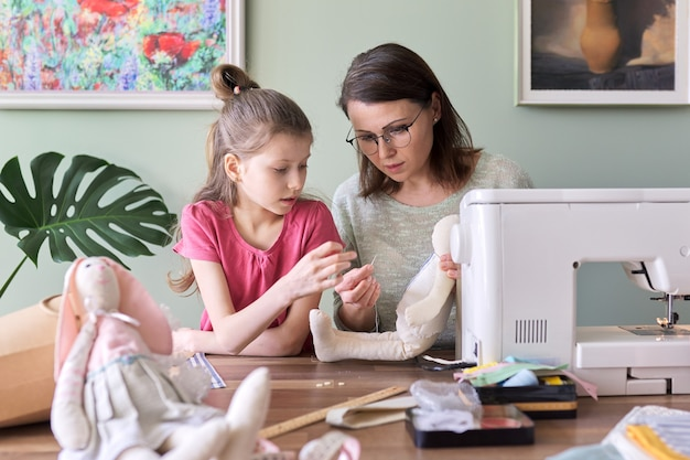 Mother and daughter child together sewing toy hare, hobbies and leisure at home. family, life, creativity, parent teaching child skills, mothers day