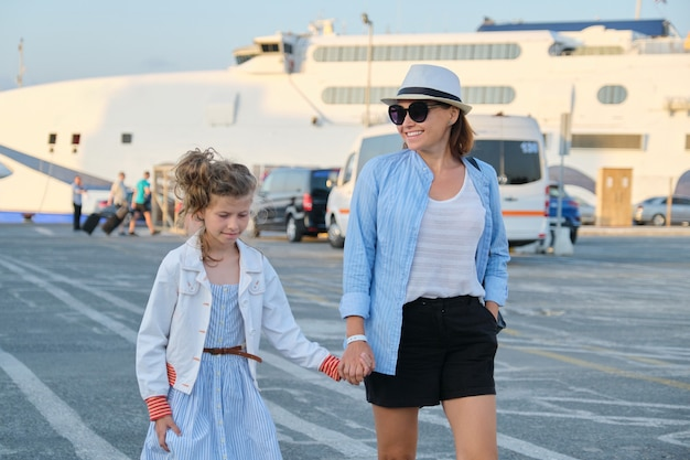 Mother and daughter child walking along seaport, family sea trip, summer vacation. sea transport, ferry at port background