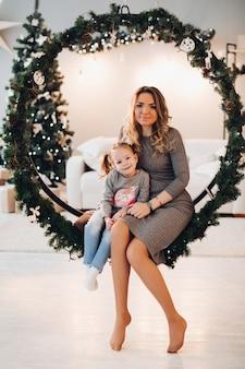 Mother and daughter on christmas swing. christmas tree.