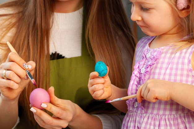 Mother and daughter coloring eggs for easter