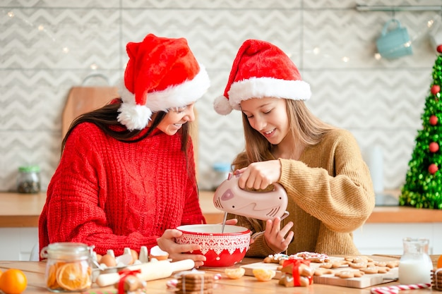 Mother and daughter cooking cookies in santa hat