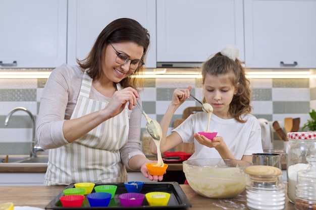 Mother and daughter cooking muffins together in home kitchen. female and child pouring raw dough into silicone molds. mothers day, family, homemade baking healthy food