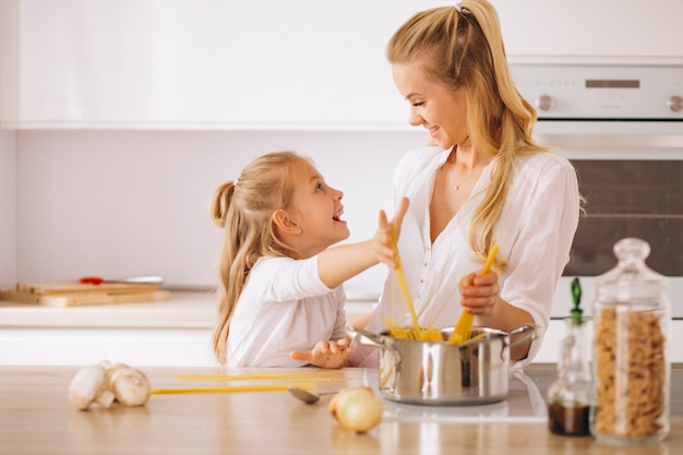 Mother and daughter cooking pasta