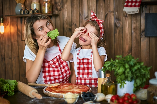 Mother and daughter cooking pizza and have fun