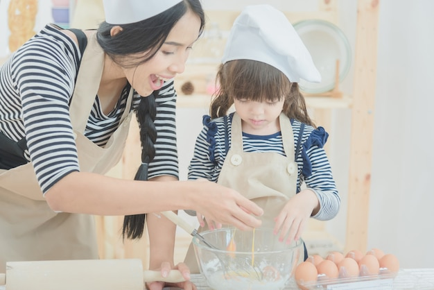 Mother and daughter cooking together to make a cake in kitchen room.