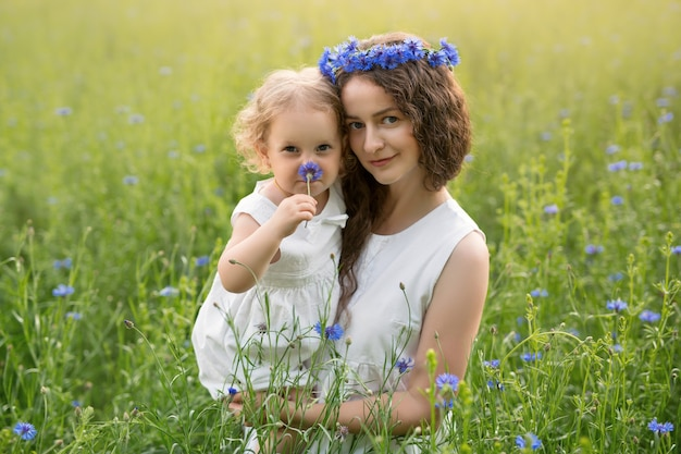 A mother and daughter in a cornflower field enjoy the fragrance of flowers.