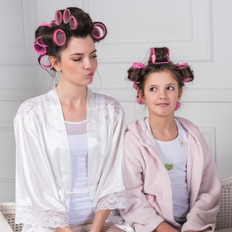 Mother and daughter in curlers looking at each other
