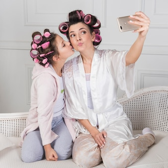 Mother and daughter in curlers taking selfie on couch