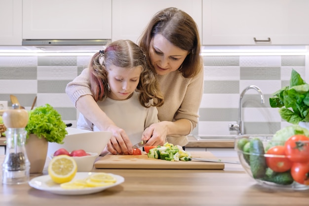 Mother and daughter cut vegetables at home in the kitchen for salad.