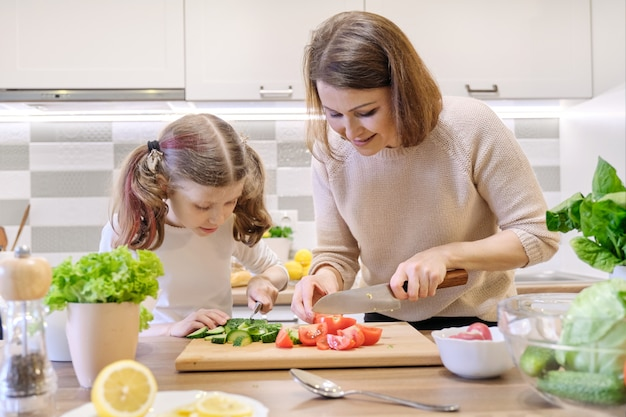 Mother and daughter cut vegetables at home in the kitchen