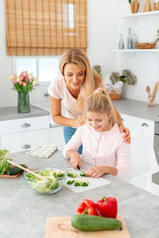 Mother and daughter cutting cucumbers