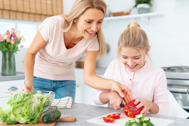 Mother and daughter cutting  peppers