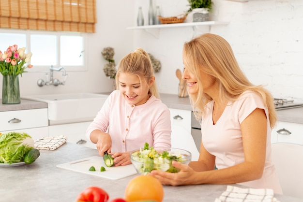 Mother and daughter cutting vegetables together