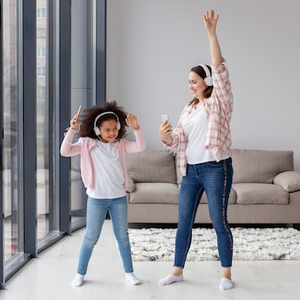 Mother and daughter dancing to music at home