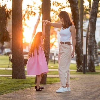 Mother and daughter dancing in the park at sunset