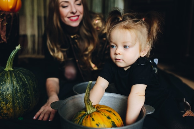 Mother and daughter decorating a pumpkin in a bowl