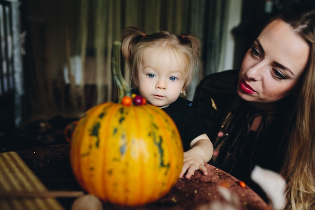 Mother and daughter decorating a pumpkin