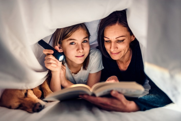 Mother, daughter and dog laying on the bed and reading book late at night