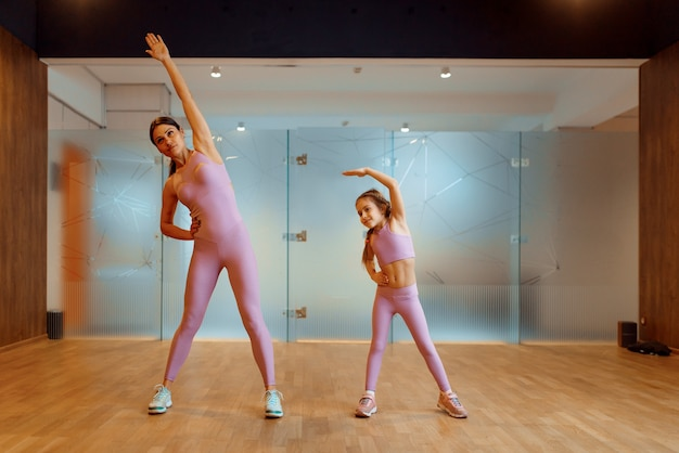 Mother and daughter doing exercise in gym, fitness workout. mom and little girl in sportswear, joint training in sport club