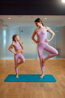 Mother and daughter doing exercise in gym, fitness workout. mom and little girl in sportswear, joint training in sportclub