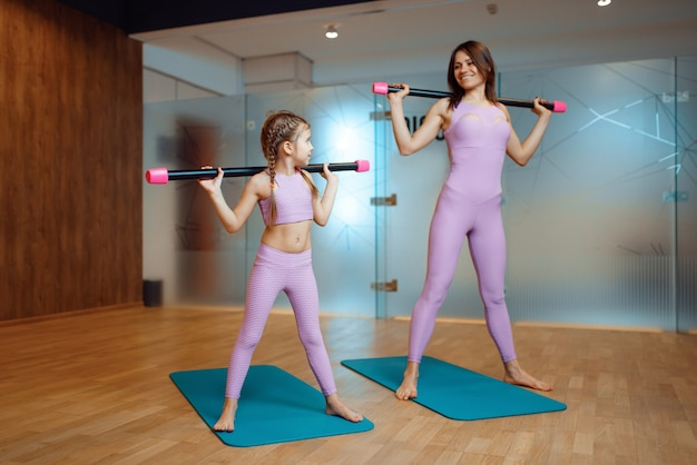 Mother and daughter doing exercise with bar on mats in gym, fitness workout. mom and little girl in sportswear, woman with kid, joint training in sport club
