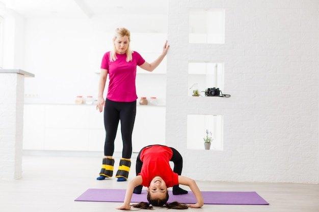 Mother and daughter doing exercises on mat at home.