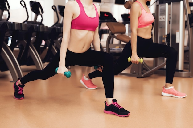 Mother and daughter doing exercises with dumbbells