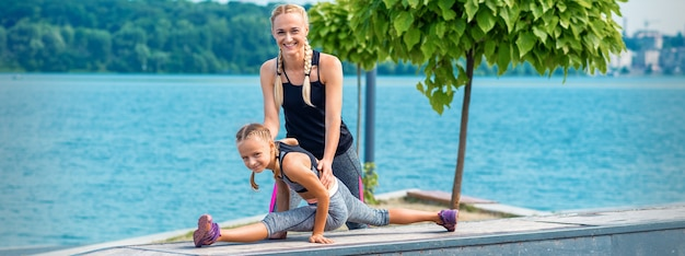 Mother and daughter doing gym exercises on the grass at the pier of the river