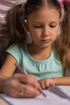 Mother and daughter doing homework from school together at home. mom helps daughter do homework