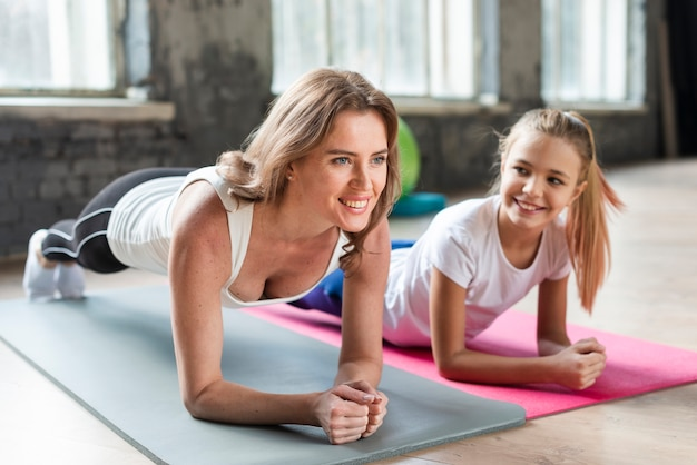 Mother and daughter doing plank on mats