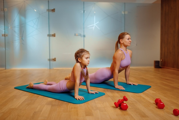 Mother and daughter doing press exercise on mats in gym, yoga workout. mom and little girl in sportswear, woman with kid, joint training in sportclub
