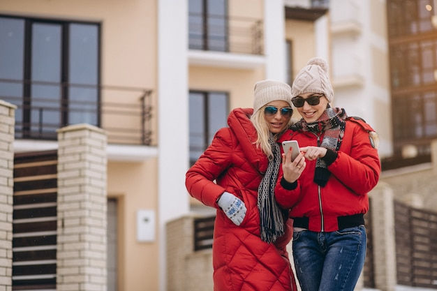Mother and daughter doing selfie outside in winter