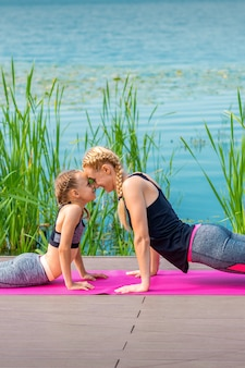 Mother and daughter doing sports exercises on the pier near the water outdoor