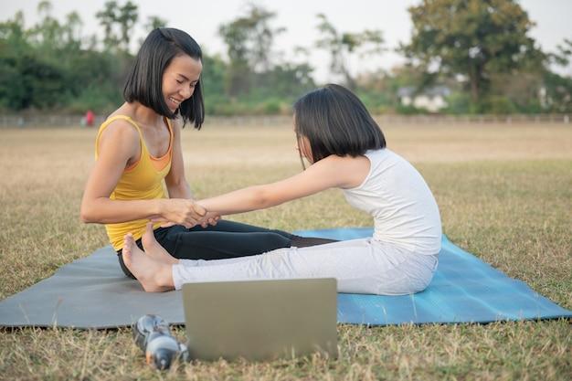 Madre e figlia che fanno yoga. formazione donna e bambino nel parco. sport all'aperto. stile di vita sportivo sano, guardare video tutorial online di esercizi di yoga e posa piegata in avanti da seduti.