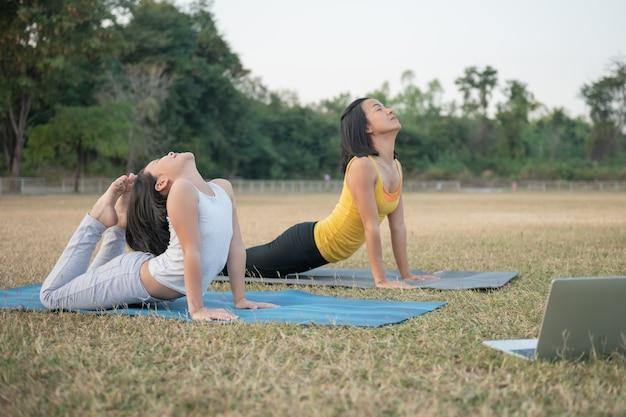 Madre e figlia che fanno yoga. formazione donna e bambino nel parco. sport all'aperto. stile di vita sportivo sano, guardare video tutorial online di esercizi di yoga e allungare il torace e la colonna vertebrale.