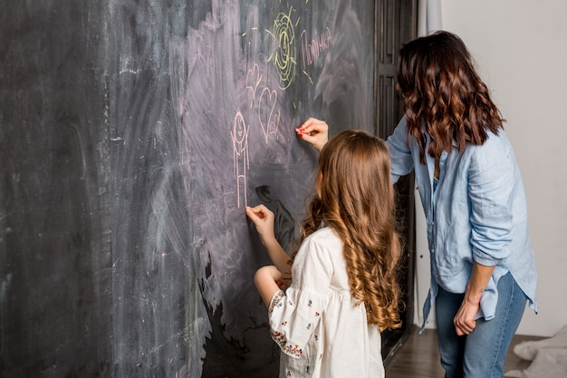 Mother and daughter drawing on blackboard