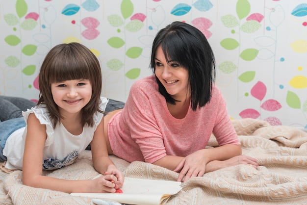 Mother and daughter drawing lying on bed