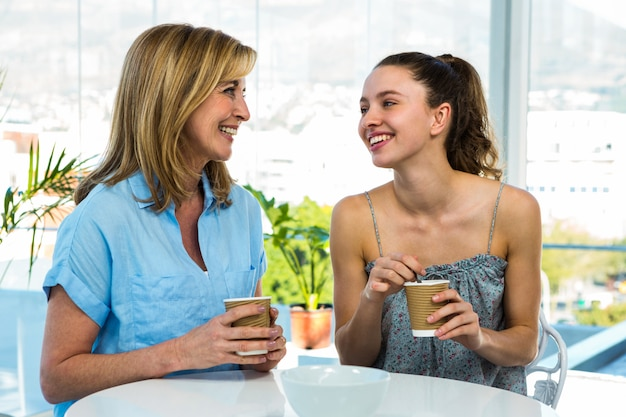 Mother and daughter drink tea at home