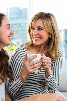 Mother and daughter drink tea in the kitchen