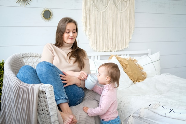 Mother and daughter drink tea together on a chair in a bright bedroom