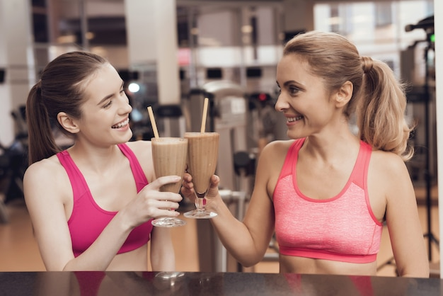 Mother and daughter drinking protein shakes at gym.