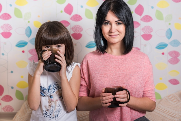 Mother and daughter drinking tea from cups