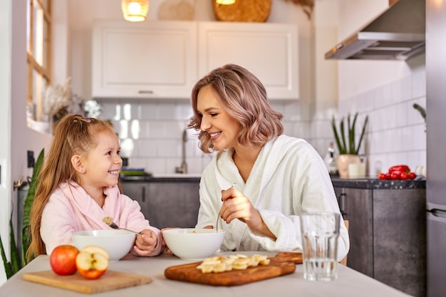 Mother and daughter eating fruit and porridge. healthy nutrition for children, morning meal.caucasian family having breakfast in a light modern kitchen