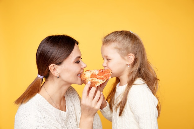 Mother and daughter eating pizza together and having fun isolated over the yellow studio.
